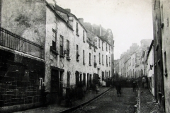 A  view of Abbey Street c.1900 looking west from the top of Mary Street. The houses on the left would later be demolished to make way for the South Presentation primary school, now the home of the Nano Nagle Place heritage centre. The large group of people are standing between the top of Greenfield Lane on the right, and the entrance to a row of houses known as Pender's Alley on the left. Image courtesy of Cork City Library.